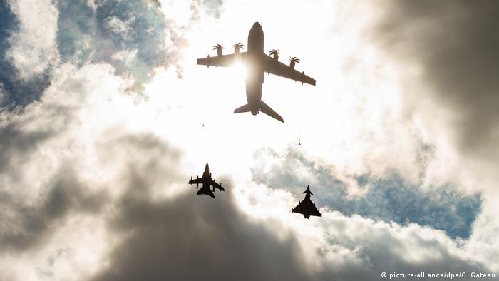 An Airbus A400M of the Bundeswehr flies in front of two fighter jets