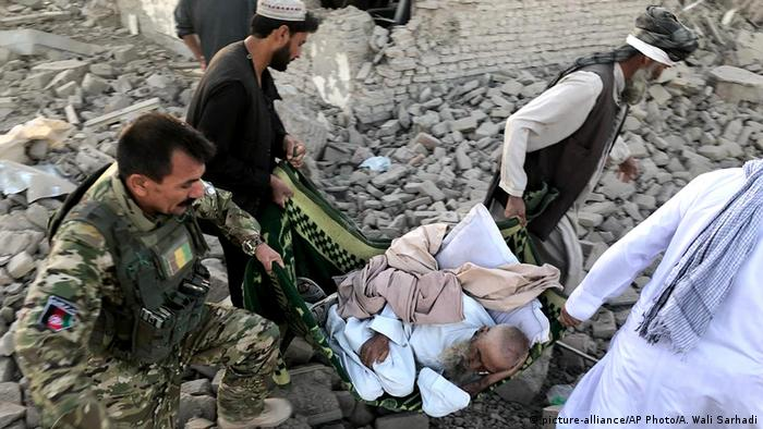 Workers search through the rubble at the site of the attack in Qalat, Afghanistan