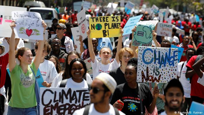 Protesters hold signs as they take part in the climate strike