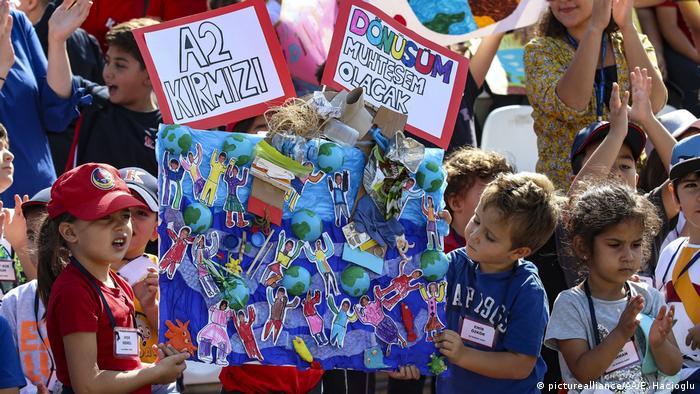 Дети держат в руках разноцветные картинки на акции в защиту климата в Анкаре