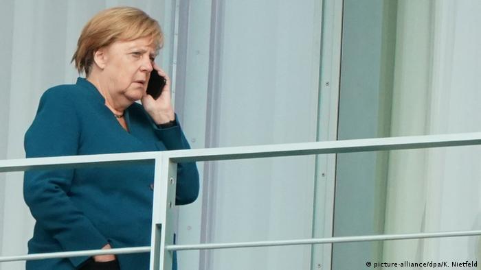 Канцлер ФРГ Ангела Меркель с телефоном в руке