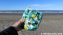 Samantha Early holds a reusable nappy with South New Brighton Beach as a backdrop