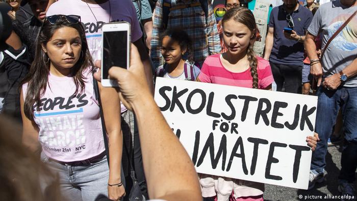 Greta Thunberg holds a protest sign in New York