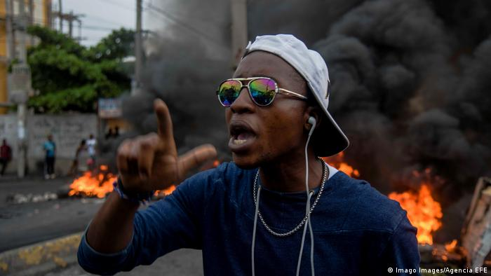 A man protesting in Haiti with a burning barricade in the background