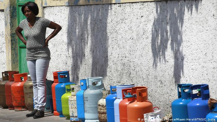 A woman stands next to empty propane tanks used to mark the owners' places in line for fuel