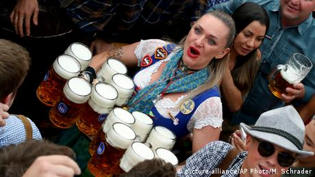 A waitress holds 12 glasses of beer during the opening of the 186th 'Oktoberfest' beer festival in Munich (picture-alliance/AP Photo/M. Schrader)
