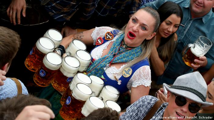 A waitress holds 12 glasses of beer during the opening of the 186th 'Oktoberfest' beer festival in Munich
