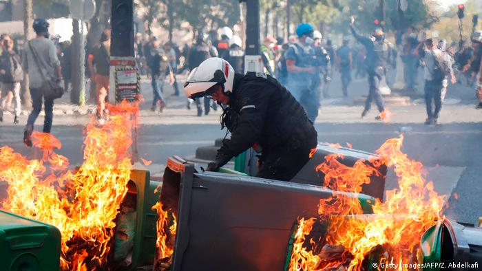 A French policeman tries to separate burning rubbish bins during protests in Paris