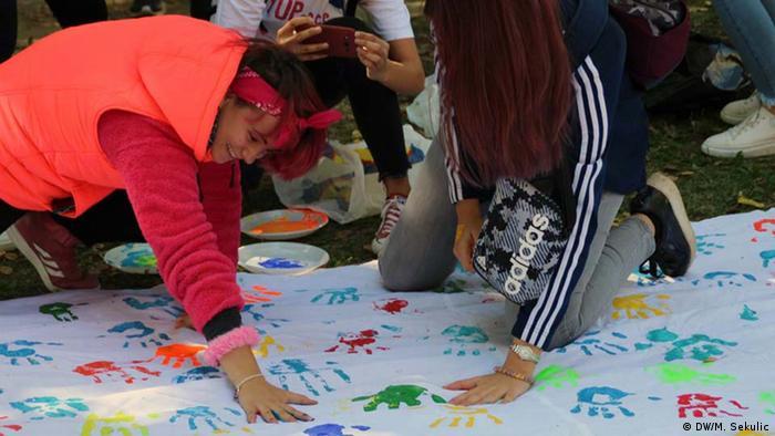 Kao znak svoje opredjeljenosti za mir mladi ostavljaju otisak svojih ruku na platnu