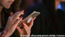 Deutschland | Frau hält ihr Smartphone | Berliner Modewoche
