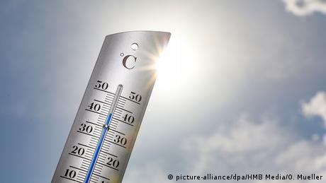 Sun rays glare into from behind a thermometer showing over 40 degrees Celcius