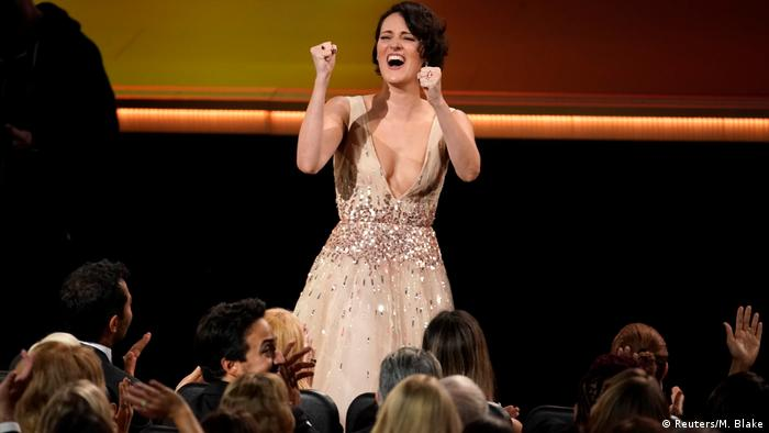 Phoebe Waller-Bridge in low-cut, glittering gown, fists clenched, cheered by onlookers (Reuters/M. Blake)