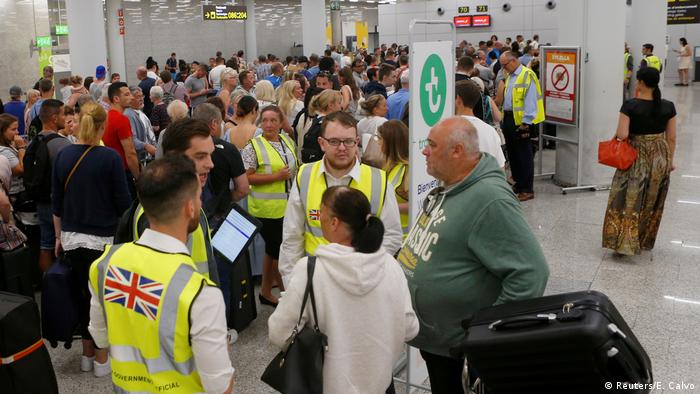 Passengers are seen waiting at the check-in points at Palma de Mallorca Airport