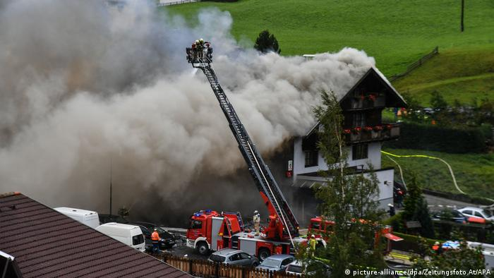 Fire brigade with ladder at fire in St. Jodok am Brenner, with smoke seen pouring from the roof of a building (picture-alliance/dpa/Zeitungsfoto.At/APA)