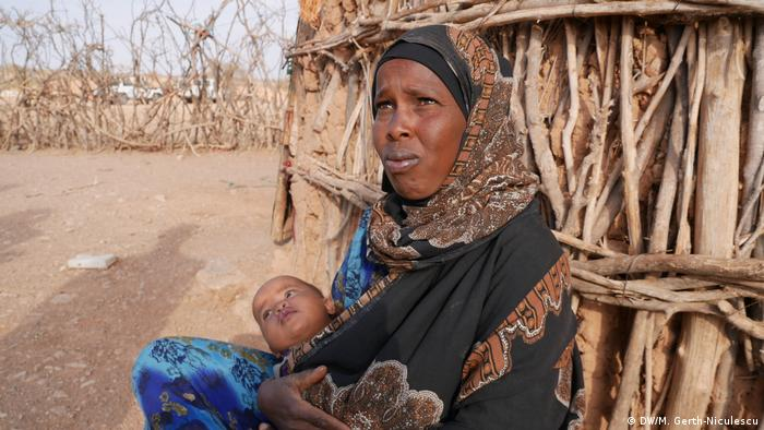 Mahaba Ibrahim sits in front of her house with her baby in Ethiopia