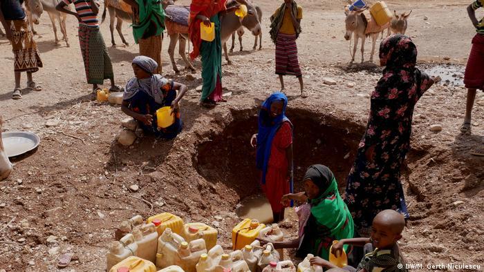 Frauen und Kinder befüllen Wasserkanister in den Resten einer fast ausgetrockneten Wasserstelle in Äthiopien