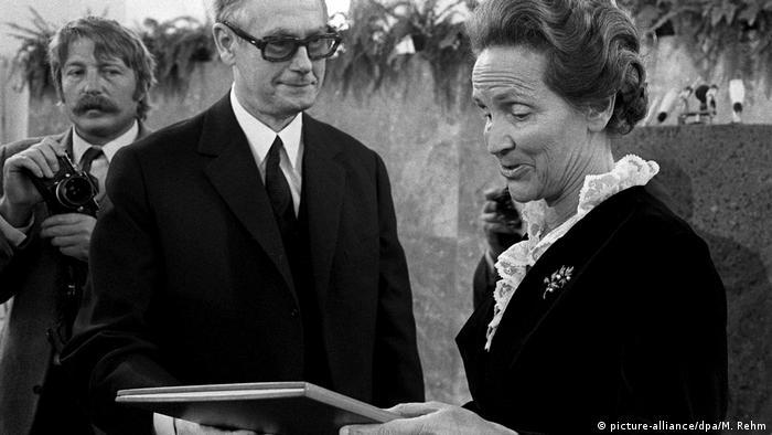 Mulher olhando para um livro sendo observada por dois homens
