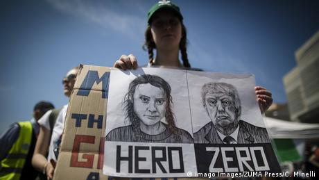 Greta Thunberg and Donald Trump faces on a placard at an environmental protest in Italy