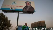 KABUL - SEPTEMBER 23 : An Afghan man sells water jugs next to a giant election billboard of Abdullah Abdullah, Chief Executive of Afghanistan who is running for President on September 23, 2019 in Kabul, Afghanistan. Afghans will go to the polls on September 28th. Afghanistan is struggling with unrelenting violence and a very high death toll for August as Presidential elections will continue to take place on September 28th. Over a week ago President Trump cancelled peace negotiations with the Taliban with a possible return to the talks still unclear after 18 years of war confusion and chaos to a solution remains. The US state department also cut $100 million in aid this week. (Photo by Paula Bronstein/Getty Images )