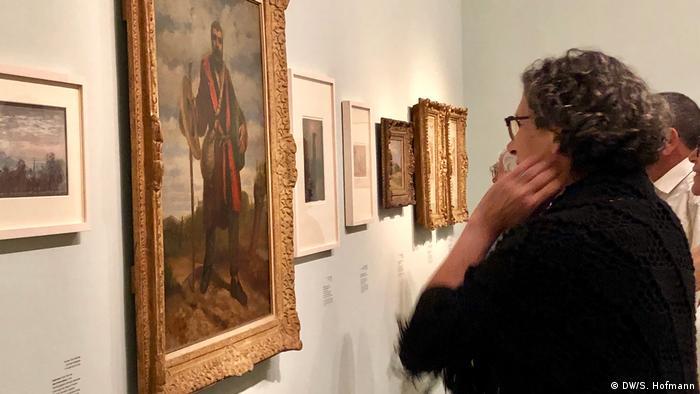 Woman inspects an artwork