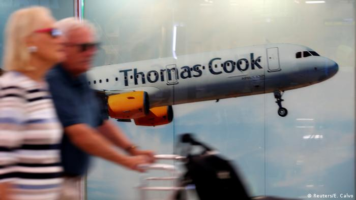 Holidaymakers stand in front of an ad for Thomas Cook
