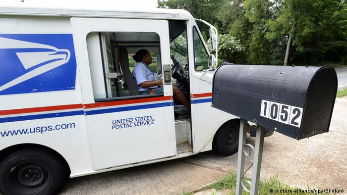 A US Postal Service driver in a delivery truck