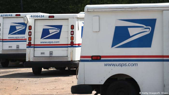 USPS trucks with the postal service logo sit in a parking lot
