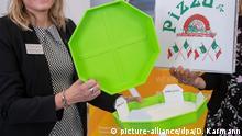 24.09.2019, Bayern, Nürnberg: Cornelia Fehlner von der Nürnberg Messe präsentiert während der FachPack 2019, die Fachmesse für Verpackungen, Prozesse und Technik, das Pizzabow. Die Pizza-Verpackung für Lieferservices ist ein Mehrwegsystem bestehend aus stapelbaren Kunststoffschalen in denen sich ein Papptablett befindet. Der größte Teil der Pappe eines herkömmlichen Kartons wird somit überflüssig. Das Papptablett wird bei Lieferung entnommen und behalten, die Schale wird wieder mitgenommen und wiederverwendet. (zu dpa Verpackungsindustrie will grüner werden) Foto: Daniel Karmann/dpa | Verwendung weltweit