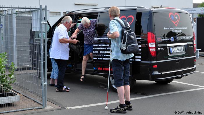 Гюнтер Хайенга помогает своим подопечным выбраться из автомобиля