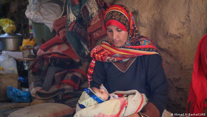 A Yemeni woman holds her baby in her arms