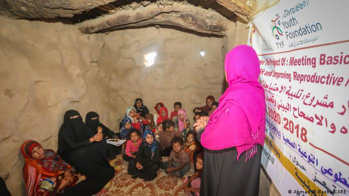 A woman speaks to a group of Yemeni women in children in a room at a session run by the NGO CARE