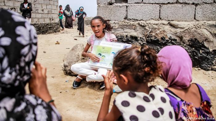 A young Yemeni girl reads to other children