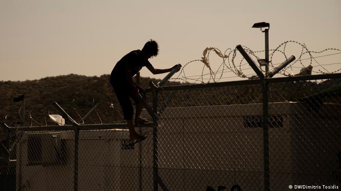 A refugee climbing down a fence