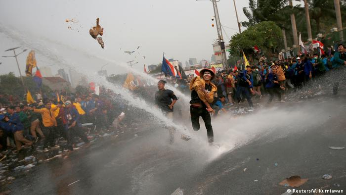 A protester throws an object at police in Jakarta