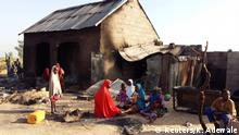 Nigeria Bilabulin Village   Einwohner sitzen an einem abgebrannten Haus nach einem Angriff von Boko Haram