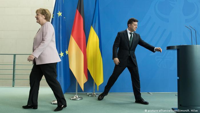 Angela Merkel walks away from Zelenskiy as he reaches towards a podium (picture-alliance/SvenSimon/A. Hilse )