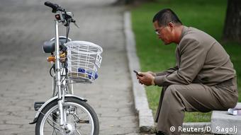 Nordkorea Mann mit Handy und E-Bike in Pyongyang