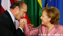 FILE PHOTO: German Chancellor Angela Merkel (R) is kissed by French President Jacques Chirac (L) as she welcomes him at the Philharmonie in Berlin, Germany, March 24, 2007. Picture taken March 24, 2007. REUTERS/Kai Pfaffenbach/File Photo