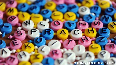 Das Wort Sprache liegt aus einzelnen Buchstaben zusammengesetzt mit weiteren Buchstaben auf einem Tisch