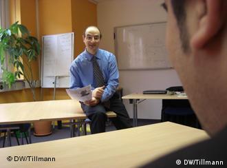 Hakan Altinok sitzt aut einem Tisch in einem Klassenzimmer (Foto: Pauline Tillmann, DW 2009)