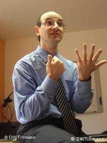 Lehrer Hakan Altinok gestikuliert mit beiden Händen und gespreizten Fingern (Foto: Pauline Tillmann, DW 2009)