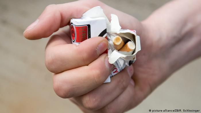 A hand crunching a pack of cigarettes