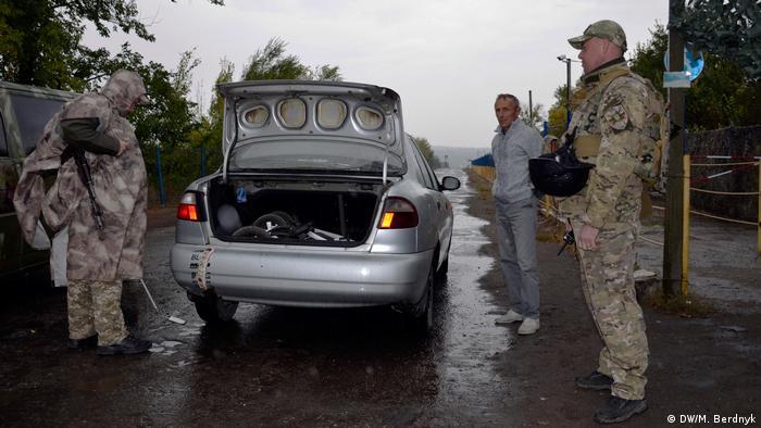 Военные проверяют автомобиль на КПП Золотое