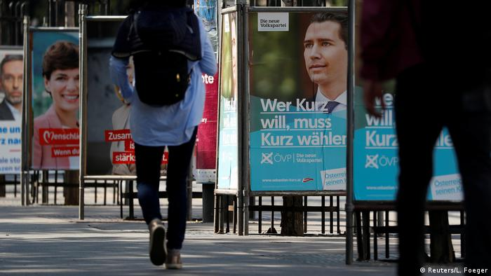 Persons pass election campaign posters of the head of Austria's Peoples Party (OeVP) former Chancellor Sebastian Kurz and Social Democrats (SPOe) party leader Pamela Rendi-Wagner in Vienna