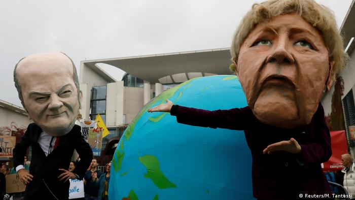 Angela Merkel and Olaf Scholz portrayed at Fridays for Future protest (Reuters/M. Tantussi)