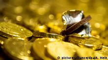 ILLUSTRATION- Ein Schokotaler liegt am 21.11.2015 in Frankfurt am Main (Hessen) in seiner zur Hälfte ausgepackten Folie. Im frühen 19. Jahrhundert machten amerikanische Schokoladenhersteller den jüdischen Brauch des Chanukka-Geldes zur Geschäftsidee und verpackten Schokoladentaler in gold- und silberfarbener Folie. Foto: Alexander Heinl/dpa | Verwendung weltweit