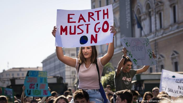 Climate protestors hold up signs