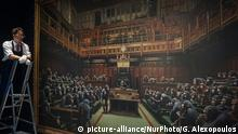 27.09.2019 *** Gallery workers pose with the Banksy painting 'Devolved Parliament' at Sotheby's on September 27, 2019 in London, England. Photo call for Banksy's Devolved Parliament painting ahead of it being offered at auction by Sotheby's. The artwork showing the House of Commons full of chimpanzees is expected to fetch GBP1.5 to GBP2 million. (Photo by Giannis Alexopoulos/NurPhoto) | Keine Weitergabe an Wiederverkäufer.
