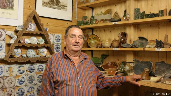 A man stands in front of shelves of tiles and ceramics