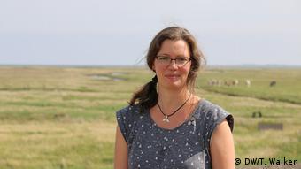 Mulher de óculos com campo de ovelhas ao fundo